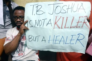 A man holds a placard to protest the coroner's inquest on October 30, 2014 at the Ikeja High Court in Lagos into the cause of the collapse at a guesthouse of the Synagogue Church of All Nations, led by TB Joshua (AFP Photo/Pius Utomi Ekpei)