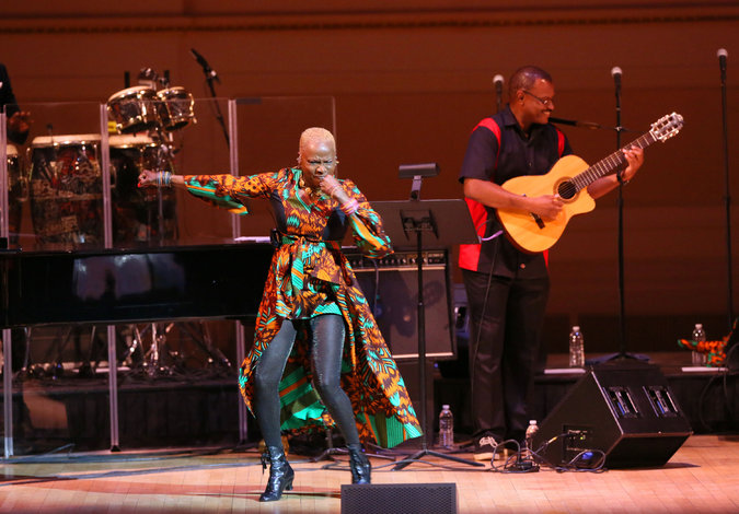 Angelique Kidjo performing with Dominic James on guitar at Carnegie Hall. Credit Ruby Washington/The New York Times