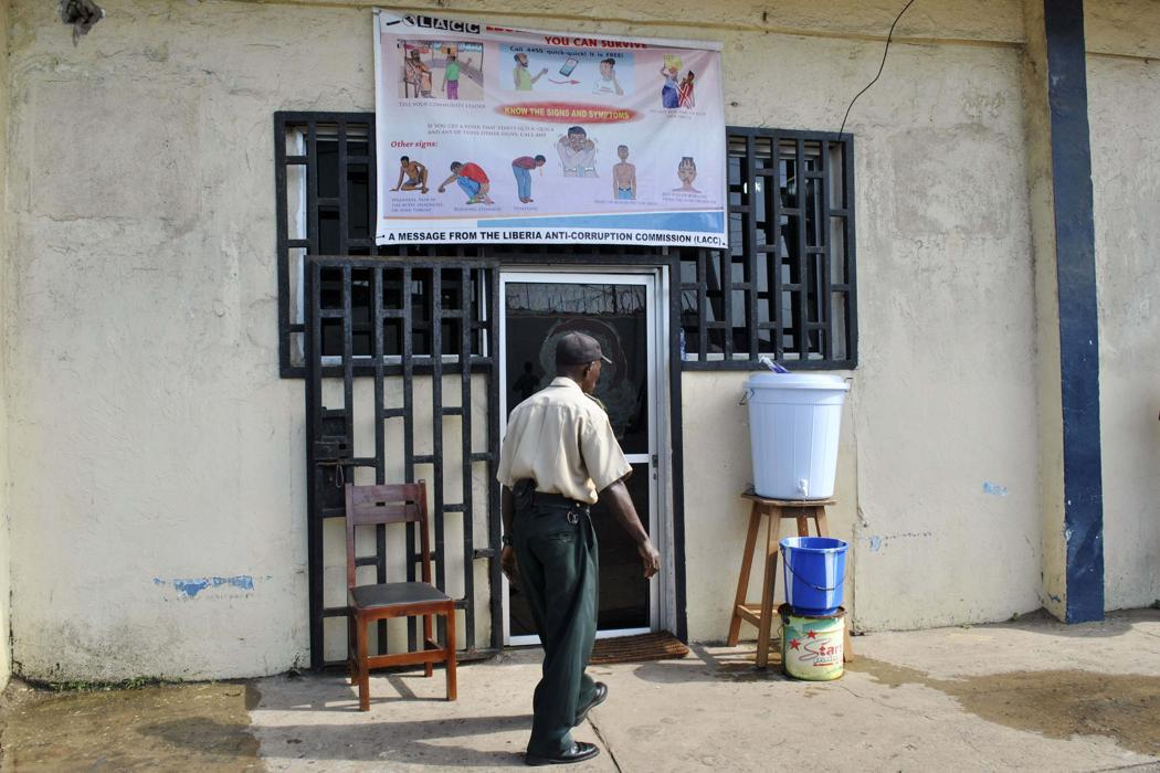 A security guard walks in front of a hand-washing facility at the entrance of a Liberian anti-corruption commission in Monrovia December 9, 2014. (REUTERS/James Giahyue)