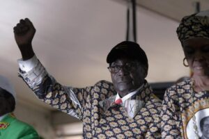 """Zimbabwean President Robert Mugabe gestures as he greets the crowd upon arrival on the last day of the Zanu PF 6th National Congress, in Harare, Sat, Dec. 6, 2014. Zimbabwe's vice president was a rebel commander known as """"Spill Blood"""" during the war against white rulers and, at the age of 25, became the youngest Cabinet minister after independence. Now she is a political pariah, accused of plotting the downfall of President Robert Mugabe with the help of nocturnal sorcery. (AP Photo/Tsvangirayi Mukwazhi)"""