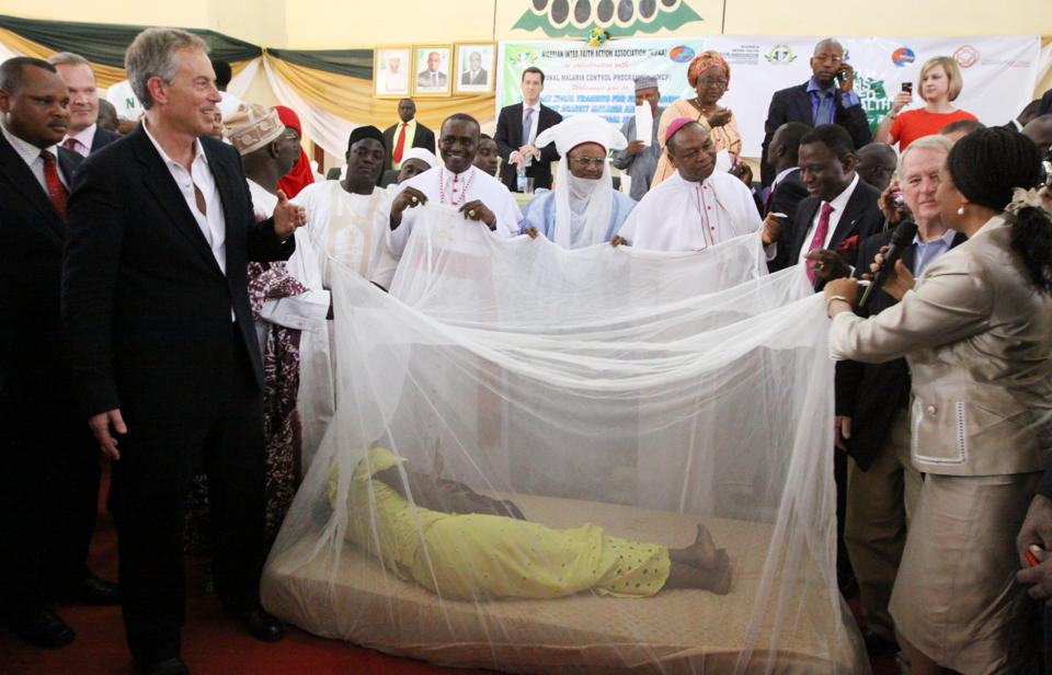 FILE- In this Saturday, Feb. 20, 2010, file photo, former British Prime Minister Tony Blair, left, former Nigerian President Olusegun Obasanjo, on Blair's left, and Religion Leaders hold a Mosquito net with a women lying inside to demonstrate the use of the net against malaria in Abuja, Nigeria. The operation to fight Ebola in West Africa has hampered the campaigns against malaria, a preventable and treatable disease that is claiming many thousands of lives. In information released Sunday Dec. 28, 2014, Dr. Bernard Nahlen, deputy director of the U.S. President's Malaria Initiative says they have had to stop pricking fingers to do blood tests for malaria, so statistics show a decrease in reported cases of maleria but the decrease is likely because people are too scared to go to health facilities and are not getting treated for malaria.(AP Photo/Sunday Alamba, FILE)