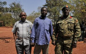 In this photo taken Friday, Jan. 16, 2015 and released by the Uganda People's Defence Force (UPDF), a man said by the UPDF to be the wanted Lord's Resistance Army (LRA) commander Dominic Ongwen, center, stands with Ugandan Contingent Commander to the African Union Regional Task Force Col Michael Kabango, right, and another unidentified man, left, prior to being handed over by the UPDF to the African Union Regional Task Force who later handed him over to Central African Republic authorities, in the Central African Republic. Central African Republic's Seleka rebels, who once overthrew the government, say they're entitled to a $5 million reward from the U.S. government because they say they captured and handed over the wanted international war crimes suspect Dominic Ongwen to American forces. (AP Photo/Uganda People's Defence Force, Mugisha Richard)