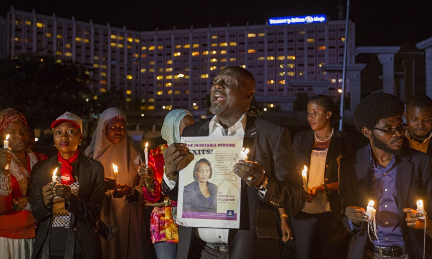 People at a vigil in Abuja hold a picture of Ameyo Adadevoh, who died after contracting Ebola while treating a Liberian-American, Patrick Sawyer. Photograph: Afolabi Sotunde/Reuters