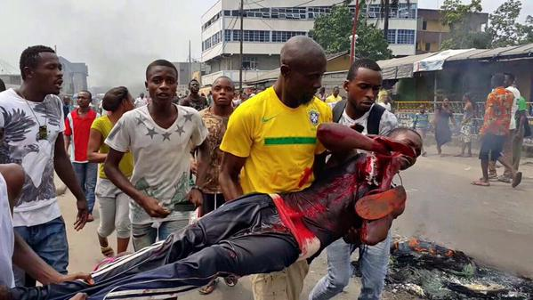 Protesters carry an injured colleague in the latest spate of violence in Kinshasa (Courtesy photo)