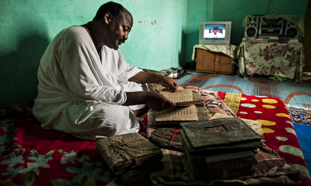 Librarian Abdel Haidara in his home in Timbuktu in 2009 with some of the manuscripts before they were taken to safety. Photograph: Brent Stirton/Getty Images