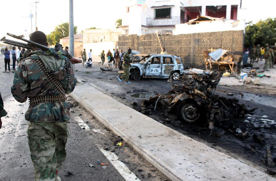 A Somalis soldier patrols near the wreckage of cars after a suicide car bomb blast on January 4, 2015 in Mogadishu (AFP Photo/Abdifitah Hashi Nor)