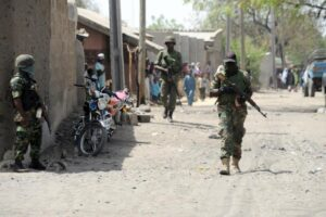 Soldiers walk on April 30, 2013 in the street in the remote northeast town of Baga, Borno State (AFP Photo/Pius Utomi Ekpei)