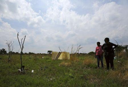 Residents stand in front of markings with sticks at an open land in Nellmapius township, 20 km (12 miles) east of Pretoria, November 13, 2014. REUTERS/Siphiwe Sibeko