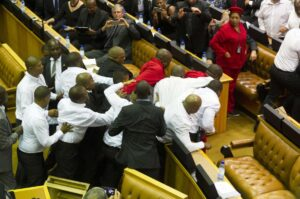 Members of Julius Malema's Economic Freedom Fighters (EFF) (in red) clash with security officials after being ordered out of the chamber during President Jacob Zuma's State of the Nation address in parliament in Cape Town February 12, 2015. The opening of South Africa's parliament descended into chaos on Thursday as security officers fought with far-left Economic Freedom Fighters (EFF) lawmakers after they disrupted President Jacob Zuma's speech. REUTERS/Roger Bosch/Pool (SOUTH AFRICA - Tags: POLITICS CIVIL UNREST)