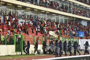 Police evacuate a tribune as the match is halted eight minutes from time.