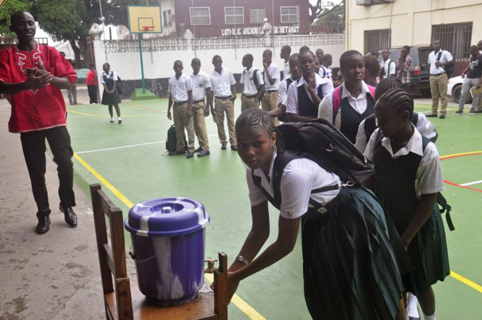 Liberian school children wash their hands before entering their classrooms as part of the Ebola prevention measures at Cathedral High School as students arrive in the morning to attend class in Monrovia, Liberia, Monday, Feb. 16, 2015. Students in Liberia began returning to the classroom Monday after a six-month closure during the Ebola epidemic that left thousands dead in this West African country.(AP Photo/Abbas Dulleh)