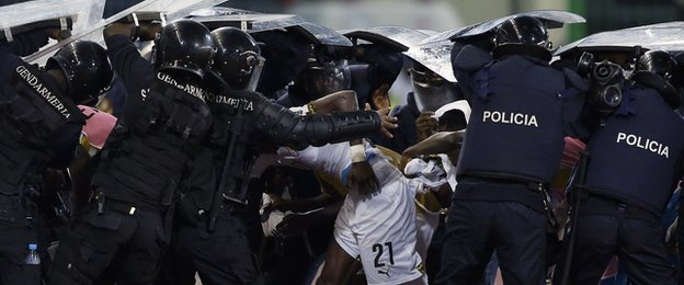 Riot police shield Ghana players as they try to come off at half-time at the Estadio de Malabo
