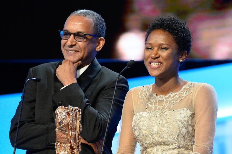 """Mauritanian director Abderrhamane Sissako (L) and screenwriter Kessen Tall smile on stage after winning the Best Original Screenplay award for """"Timbuktu"""" during the 40th edition of the Cesar Awards ceremony on February 20, 2015 in Paris (AFP Photo/Bertrand Guay)"""