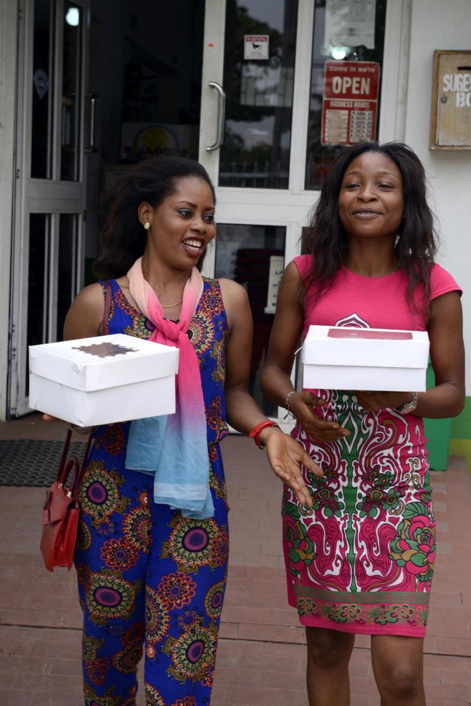 Two women walk holding Valentine cakes bought at a Lagos supermarket on February 12, 2015 (AFP Photo/Pius Utomi Ekpei)
