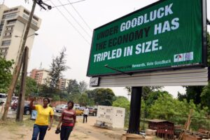 Two women walk past a campaign billboard of Nigeria's President Goodluck Jonathan and candidate for his re-election for the ruling People Democratic Party (PDP), in the Ikoyi district of Lagos, on February 24, 2015 (AFP Photo/Pius Utomi Ekpei)