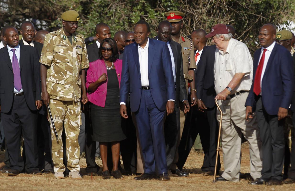 """Kenya's President Uhuru Kenyatta (C) looks on as 15 tonnes of ivory confiscated from smugglers and poachers is burnt to mark the World Wildlife Day at the Nairobi National Park March 3, 2015. The United Nations on December 20, 2013, declared 3rd March World Wildlife Day as a celebration of wild fauna and flora and to raise awareness of illegal trade. The 2015 theme for World Wildlife Day is """"Wildlife Crime is serious; let's get serious about wildlife crime"""". REUTERS/Thomas Mukoya (KENYA - Tags: SOCIETY CRIME LAW POLITICS ANNIVERSARY ENVIRONMENT ANIMALS)"""