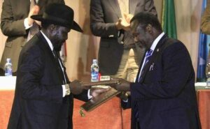 South Sudan's President Salva Kiir (L) and South Sudan's rebel commander Riek Machar exchange documents after signing a ceasefire agreement during the Inter Governmental Authority on Development (IGAD) Summit on the case of South Sudan in Ethiopia's capital Addis Ababa, Feburary 1, 2015. REUTERS/Tiksa Negeri