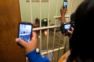 People take pictures of Nelson Mandela's former cell at Robben Island on December 13 2013 (AFP Photo/Rodger Bosch)