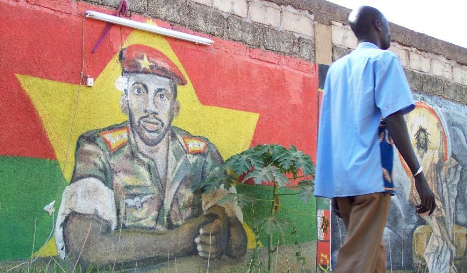 A man walks past a painting featuring military captain Thomas Sankara (L) in Ouagadougou on November 18, 2010 (AFP Photo/Ahmed Ouoba)