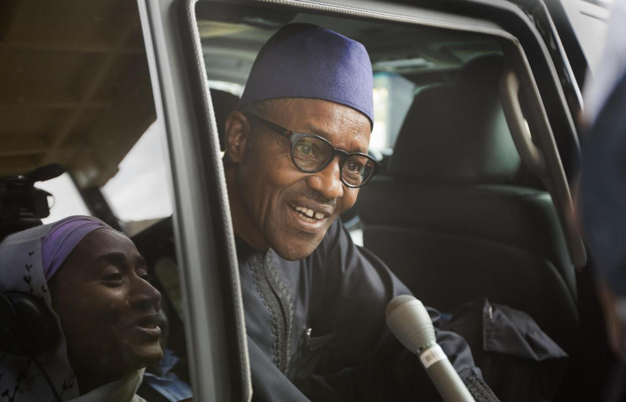 """Nigerian opposition candidate Gen. Muhammadu Buhari speaks to reporters as he gets into his vehicle after signing a joint renewal with President Goodluck Jonathan of their pledge to hold peaceful """"free, fair, and credible"""" elections, at a hotel in the capital Abuja, Nigeria Thursday, March 26, 2015. Nigerians are due to go to the polls to vote in presidential elections on Saturday. (AP Photo/Ben Curtis)"""