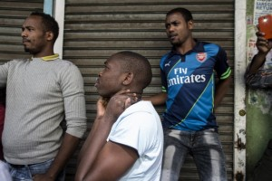 Foreigners, mostly Ethiopians, stand in front of closed shops owned by foreign nationals in Johannesburg central business district on April 14, 2015 (AFP Photo/Marco Longari)