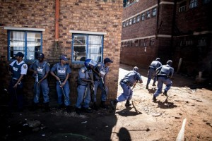 South African anti-riot policemen raid a hostel in Benoni, outside Johannesburg, on April 16, 2015, whose local residents have been protesting against the presence of Foreign-owned shops in the area (AFP Photo/Marco Longari)