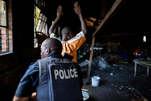 A resident raises his hands as a South African anti-riot police officer raids a hostel in Benoni on April 16, 2015 (AFP Photo/Marco Longari)