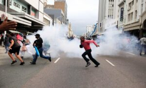 """People run for cover from a stun grenade and tear gas after a skirmish between locals and foreign nationals as thousands of people take part in the """"peace march"""" against xenophobia in Durban, South Africa, on April 16, 2015 (AFP Photo/)"""