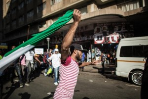 A man runs holding a Nigerian flag as thousands march against the recent wave of xenophobic attacks in South Africa through the streets of Johannesburg on April 23, 2015 (AFP Photo/Gianluigi Guercia)