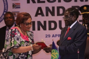 Zimbabwean President Robert Mugabe, right, hands over a ceremonial key to SADC Excecutive Secretary Stergomena Lawrence Tax during the official opening of the Southern African Development Community(SADC) Heads of State and Government Extraordinary Summit on Industrialisation in Harare, Wednesday, April, 29, 2015. The summit was called by heads of state in an effort to craft a strategy for industrialisation in the region through value addition and beneficiation of abundant natural resources in Africa. (AP Photo/Tsvangirayi Mukwazhi)