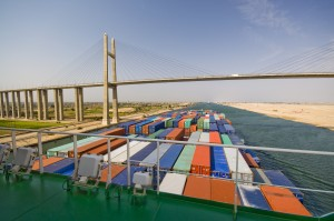 A container ship passes under the Suez Canal Bridge. Panalpina is set to acquire its Egyptian agent Afifi, a family-owned company specializing in freight forwarding, customs clearance and logistics: