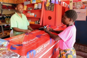 The Pafupi savings account is designed for low-income people in rural areas, especially women with no previous access to a bank account. Here, a client accesses her mobile savings account through an agent at her local market - Credit: Women's World Banking