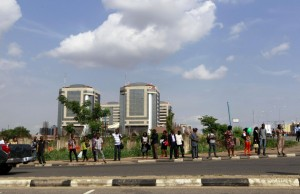 People wait at a bus stop, as fuel scarcities persist in Abuja, Nigeria May 25, 2015. Chronic fuel shortages in Nigeria brought phone firms, banks and flights to a standstill on Monday, just four days before Muhammadu Buhari's inauguration as president of Africa's biggest economy and top oil exporter. REUTERS/Afolabi Sotunde