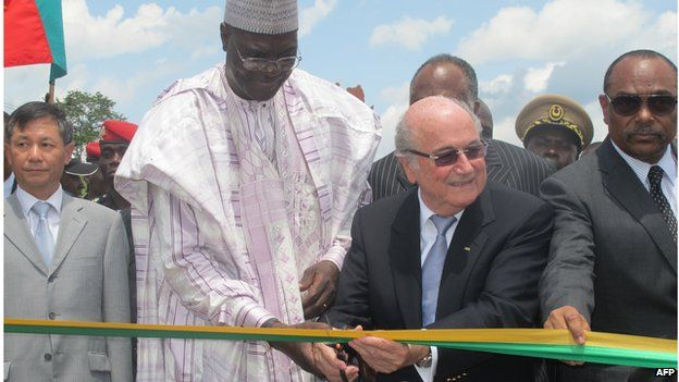 Sepp Blatter - here with Cameroon's sports minister - has overseen massive investment in facilities in Africa