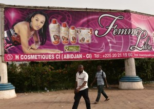 Two men walk under a giant advertisement for skin-lightening products in Abidjan on May 2, 2015 (AFP Photo/Sia Kambou)