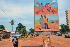 """""""Let Us Reconcile"""" implores a banner on a statue at the entrance to the main market in Bangui, in a Muslim neighbourhood that gave refuge to people fleeing religious strife that swept the Central African Republic (AFP Photo/Patrick Fort)"""