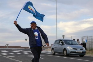 A Democratic Alliance supporter waves the party's flag outside the Colorado polling station in Mitchells Plain on the Cape Flats on May 7, 2014 (AFP Photo/Jennifer Bruce)