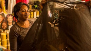 "Haddi, a naturalized citizen from The Gambia, West Africa, helps a customer at her boutique in the Malcom Shabazz ""African Market"" in Harlem, New York. Haddi, who asked just to be identified by her first name, moved with her husband to New York 27 years ago. Though she says she has a college degree and worked in a bank back home, she ended up working on a factory assembly line in the U.S. (Ed Lefkowicz)"
