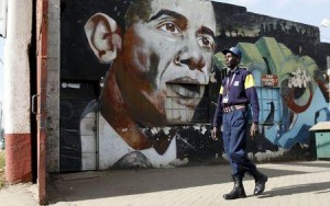 A security guard walks past a wall mural depicting U.S. President Barack Obama outside the Go-Down Art Centre in Kenya's capital Nairobi, July 17, 2015. REUTERS/Thomas Mukoya