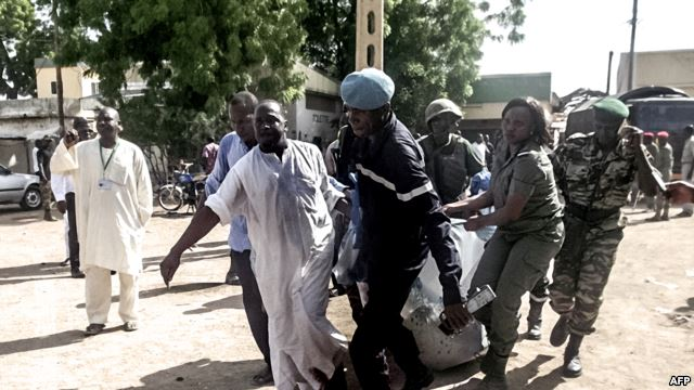 Security forces use a blanket to transport the remains of some of the 11 victims of a double blast in the northern Cameroonian city of Maroua, July 22, 2015.