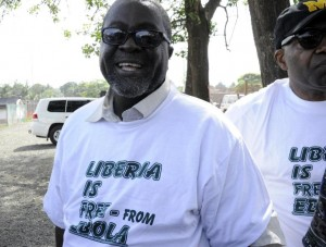 "Information minister Lewis Brown wears a t-shirt reading, ""Liberia is free from Ebola"" during a ceremony hosted by the World Health Organization in Monrovia on May 9, 2015 (AFP Photo/Zoom Dosso)"