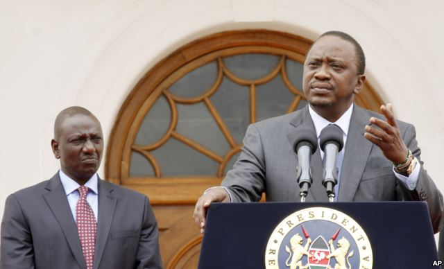 FILE - Kenya's President Uhuru Kenyatta, right, accompanied by Deputy President William Ruto, left, speaks to the media about the upcoming visit of U.S. President Barack Obama at State House in Nairobi, Kenya, July 21, 2015.