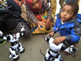 Young Ethiopian with robot whose AI software was created in his country. (courtesy of iCog Labs)