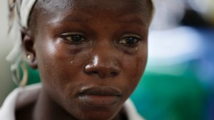 In this photo taken on Aug. 11, Ebola survivor Victoria Yillia cries as she recalls her family members who died of Ebola. She delivered her child just a few minutes' walk from the ward where just last year she had hovered between life and death. (Sunday Alamba/Associated Press)