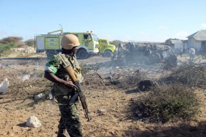 An African Union Mission in Somalia (AMISOM) soldier stands guard close to destroyed vehicles following a suicide attack which targeted a convoy of African Union troops on September 8, 2014 (AFP Photo/Abdulfita Hashi Nor)