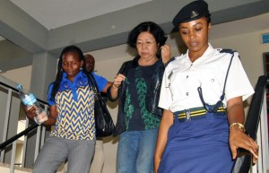 In this photo taken on Wednesday Oct. 7, 2015, Chinese national Young Feng Glan , center, is escorted by police from Kisutu Resident's Magistrate Court in Dar es Salaam, Tanzania. A Chinese woman has been charged in a Tanzanian court with smuggling nearly 1.9 tons of ivory as wildlife activists applauded the move by Tanzanian authorities to crack down on the illegal ivory trade, which has devastated the elephant population in just a few years. Businesswoman Yang Feng Clan, 66, was charged Wednesday in Dar es Salaam alongside two Tanzanian men. The three suspects allegedly committed the crime between Jan. 1, 2000 and May 22, 2014. Their case was adjourned to Monday. (AP photo)