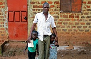Isha Ssemata, the father of Ugandan boy Mohammad Luwasi, who Ugandan authorities claim has been trafficked to the US, poses at his home in Uganda's Sonde village with his other children Latifa and Rahmah (AFP Photo/Amy Fallon)
