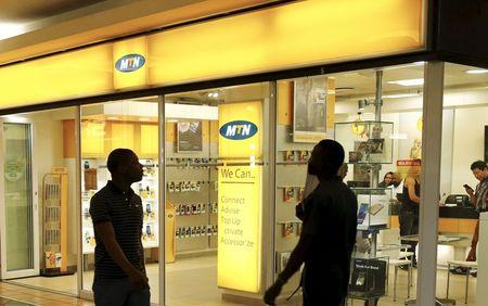 Bystanders walk past an outlet of South Africa's MTN Group in downtown Cape Town, November 10, 2015. REUTERS/Mike Hutchings