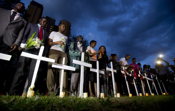 Kenyans light candles next to a white wooden cross for each of the victims of the Garissa attack, during a vigil at Uhuru Park in Nairobi, Kenya Tuesday, April 7, 2015. Students and other Kenyans gathered at dusk to honor and remember the victims, lighting candles, holding flowers, reading their names aloud, and erecting a white wooden cross for each of those who were killed in the Garissa University College attack.