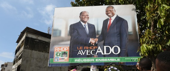"Two women look at a campaign poster that reads, ""The RHDP is with the ADO togther we can succeed"" (""ADO"" for Alassane Dramane Ouattara) presenting the candidates of the Rally of Houphouetists for Democracy and Peace (RHDP) Ivorian President Alassane Ouattara (ADO) (R) and Albert Toikeusse Mabri of the Union President for Democracy and Peace in Cote d'Ivoire (UDPCI) on October 9, 2015 in Kumasi, a popular district of Abidjan. Ivory Coast's presidential election will take place in a ""peaceful climate"", President Alassane Ouattara in Abidjan, ahead of October 25 polls seen to be crucial for stability after a decade of political and military crisis. AFP PHOTO / SIA KAMBOU        (Photo credit should read SIA KAMBOU/AFP/Getty Images)"